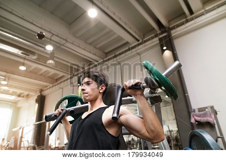 Young fit hispanic man in gym working out on fitness machine, flexing muscles. Bodybuilder training, doing shoulder press.