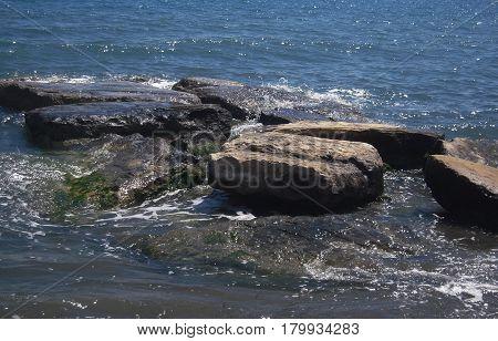 Sea foam, Blue water  and brown rocks. Freshness andsea breeze.