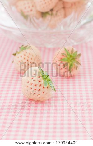 Pineberries or Hula Berry a hybrid strawberry with a pineapple flavor white flesh and red seeds focus on the front berry
