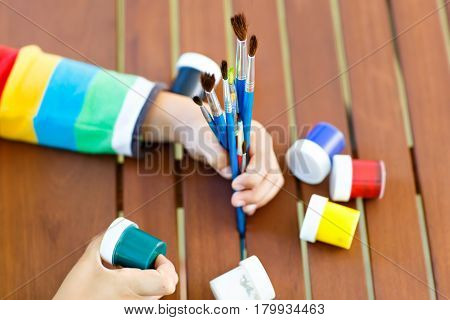 Close-up of hands of kid holding watercolors and brushes. child and student is back to school. Education, school, learning concept. School, preschool nursery equipment