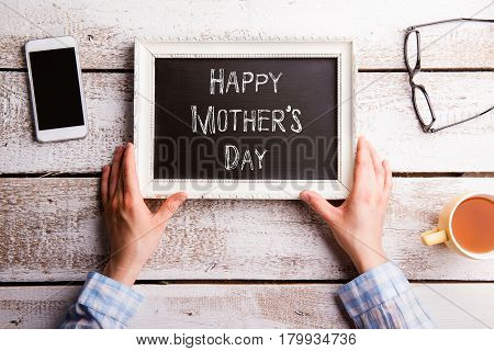 Hands of unrecognizable woman holding white picture frame with chalk Happy mothers day sign. Smart phone, eyeglasses, cup of tea. Studio shot on wooden background. Flat lay.