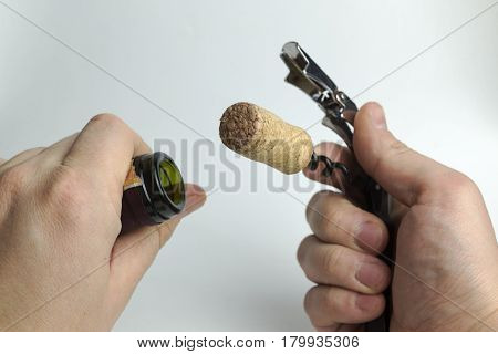 The hand holds a corkscrew on a white background.