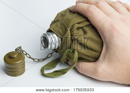 Man holding army water canteen isolated on a white background