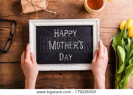 Hands of unrecognizable woman holding white picture frame with chalk Happy mothers day sign. Bouquet of yellow tulips, little package, eyeglasses and cup of tea. Studio shot on wooden background.