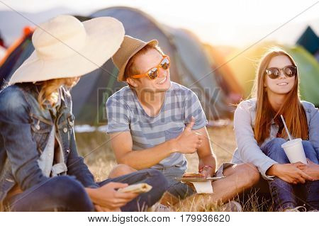 Group of teenage boys and girls at summer music festival, sitting on the ground in front of tents eating