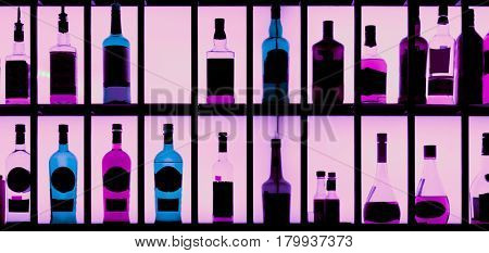Various hard alcohol bottles in a bar, back lighting, toned image