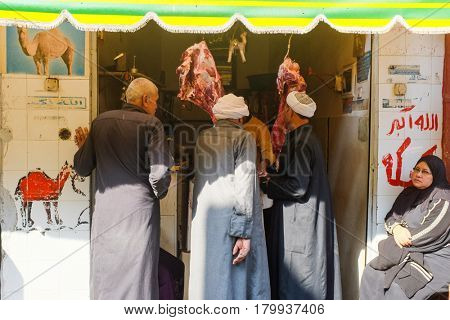 CAIRO, EGYPT - JANUARY 23, 2016: A local butcher and customers in traditional local clothes in the Capital City Cairo, Egypt.