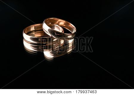 Closeup of Two classical gold wedding rings on isolated black mirror background with copy space on a wedding day. Love and marriage proposal concept.