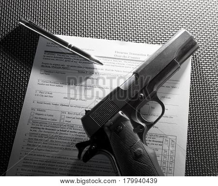 Pen and handgun with the form to purchase a firearm