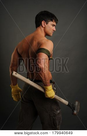 The tough construction man is holding a hammer.