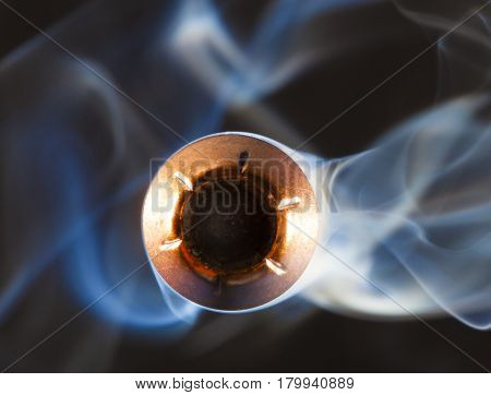 Hollow point with a copper jacket and smoke behind