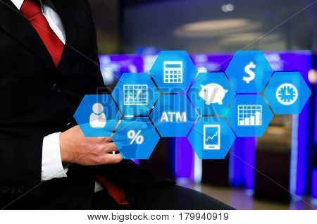 businessman in suit and red necktie using smart phone with finance icon financial technology and business concept on abstract blurred background of ATM Machine for withdraw or deposit cash money.