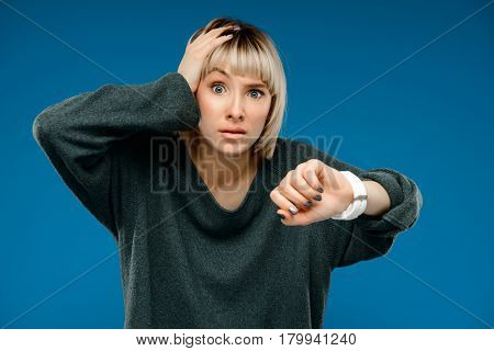 Portrait of young blonde pretty girl in green sweater looking at watch, surprised, over blue background.