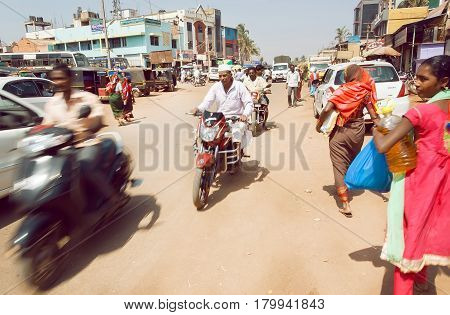 BADAMI, INDIA - FEB 8, 2017: Mothion blur from rushing vehicles on busy Indian street with pedestrians and bikes in city of Karnataka state on February 8, 2017. Population of Karnataka is 62000000 people