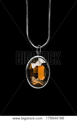 Vintage yellow crystal medallion on a chain isolated over black