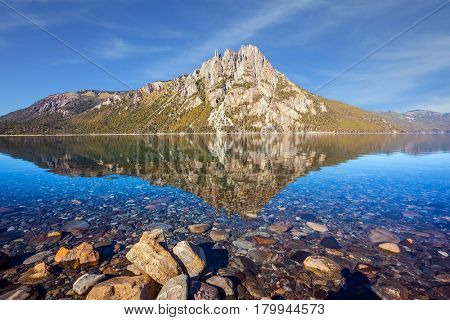 Picturesque pyramidal mountain in the city of San Carlos de Bariloche, Argentina. The mirror water of shallow lake reflects sharp peaks and rocks. The concept of exotic and extreme tourism