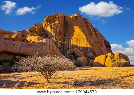 The granite outcrops in the Desert Namib. Stone of Spitzkoppe, Namibia. Play of light and shadow on the rocks. Concept of extreme and ecological tourism