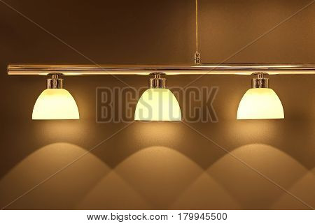 Soft light from the elegant fashionable lamp draws on a wall