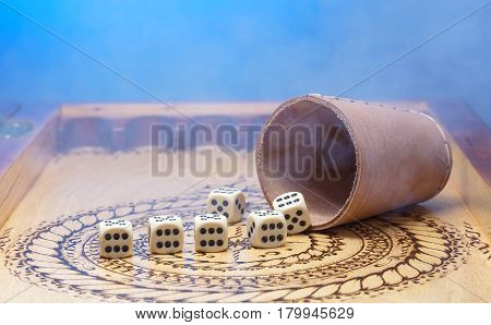 image of elements of gambling on a carved wooden board,Figures six, blue background, smoke