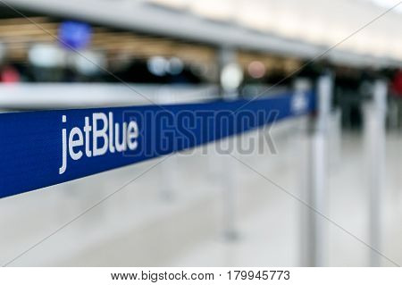 New York March 18 2017: Stanchion with the jetBlue signage on the band is seen at the jetBlue terminal of the JFK airport.