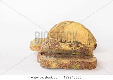 Slices of old stale moldy rye bread on wooden shelf