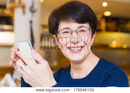 Attractive smiling woman using mobile phone in cafe