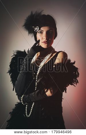 Portrait of a beautiful young woman in style of the great Gatsby of the 20s. Vintage clothing and jewelry poster