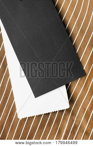 Black and white blank labels on brown striped cloth