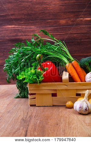 Vegetables. Potatoes, carrot and red pepper. Lettuce salad, garlic and brocoli. Natural organic bio food. Wooden basket on rustic table.