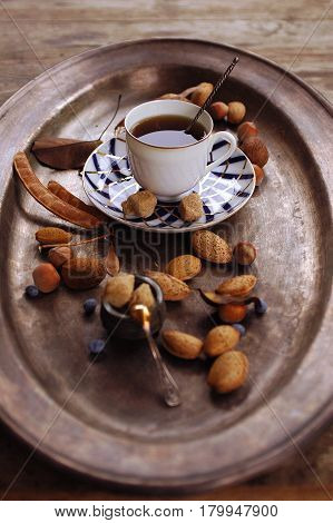 charming vintage still life with Coffee in a porcelain cup, almonds, hazelnuts brown sugar and blueberries  on a bronze dish