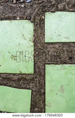 Closeup of obsolete tile background with green tiles in stone
