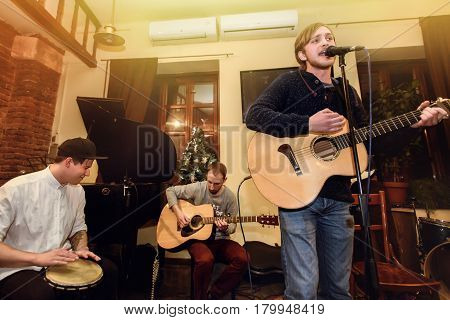 Stylish Acoustic Band Of Young Men Playing And Singing On A Stage