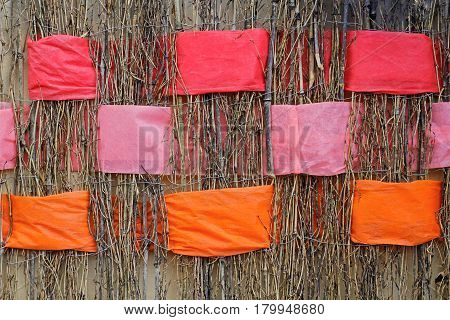 Background of twigs with interwoven wide orange pink and coral ribbons of felt