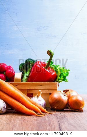 Vegetables. Carrot and red pepper. Garlic, onion and brocoli. Lettuce salad and red radish. Wooden basket on blue background.