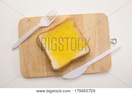 sweet toast butter on wooden chopping board with knife and fork on white background. this bread is Thai style sweetmeat.
