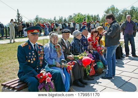 Volgograd Russia - May 09 2008: World War II veterans sit on the bench with flowers on the Mamaev Kurgan in Volgograd