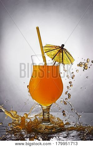 Splash In Glass Of Orange Alcoholic Tropical Cocktail Drink With Umbrella And Straw