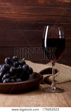 Red wine in Wineglass with dark grapes branch on plate. On rustic wooden background.