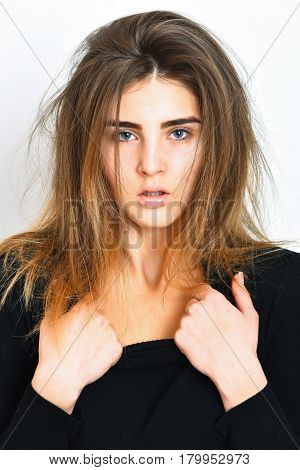 pretty cute sexy brunette girl or caucasian woman with ruffled hair posing in black sweater on white studio background