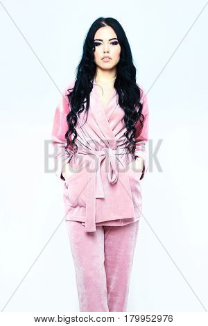 pretty cute sexy girl or beautiful woman with fashion makeup on serious face and curly long hair posing in womans pink velour pajama home suit isolated on white background
