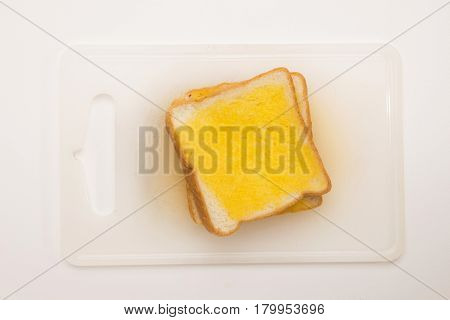 sweet toast butter meal on white chopping board with on white background. this bread is thai style sweetmeat.