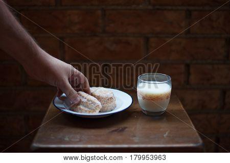Man hand grabbing a sweet and milk, brick background