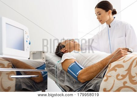 You are in safe hands. Low angle of serene female physician calming nervous client under glass dropper in clinic