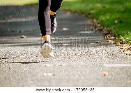 running, jogging or walking in park, feet closeup