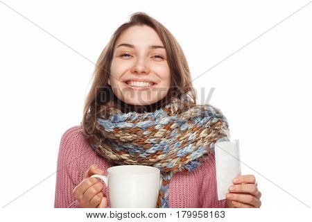Young female in scarf holding mug and prescription and looking happy after taking medicament.