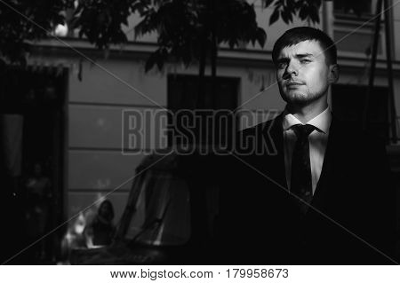 Handsome groom in black stylish suit with red tie posing outdoors at sunset portrait of serious businessman in elegant clothing