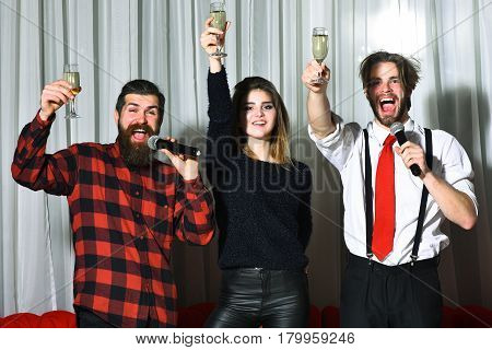 Happy friends celebrating at karaoke party on white curtain. Smiling pretty girl or beautiful woman and two bearded men hipsters with beards in red plaid shirt and suit pants with suspenders singing