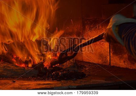 Flames blaze brightly inside the dark coal forge as the blacksmith carefully guides the metal with tongs