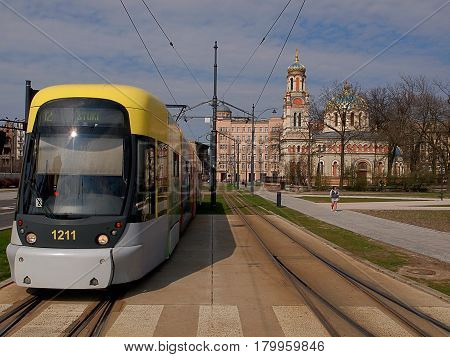 Tram and Orthodox church. Lodz, Poland - March 31, 2017 Modern urban tram at a large intersection in Lodz .
