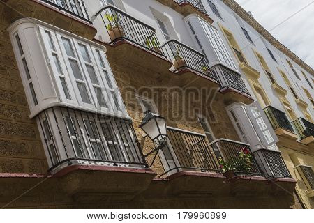 Detail of balconies and large windows on the time of the nineteenth century Narrow street with traditional architecture in Cadiz Andalusia southern Spain